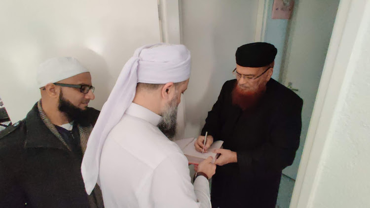Shaykh Muqaddami having his booked signed